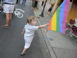 A young boy waves a rainbow colored flag at a Pride Parade in Shadyside