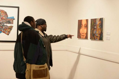 """Guests of the opening reception for """"Exposure: Black Voices in the Arts"""" interact with the art. Meghan Sunners 