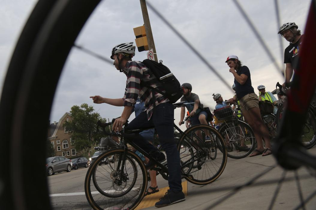 Mike Carrol from Wilkinsburg directs a pack of cyclists riding in protest of PennDOT across Forbes Avenue. |Theo Schwarz / Senior Staff Photographer.