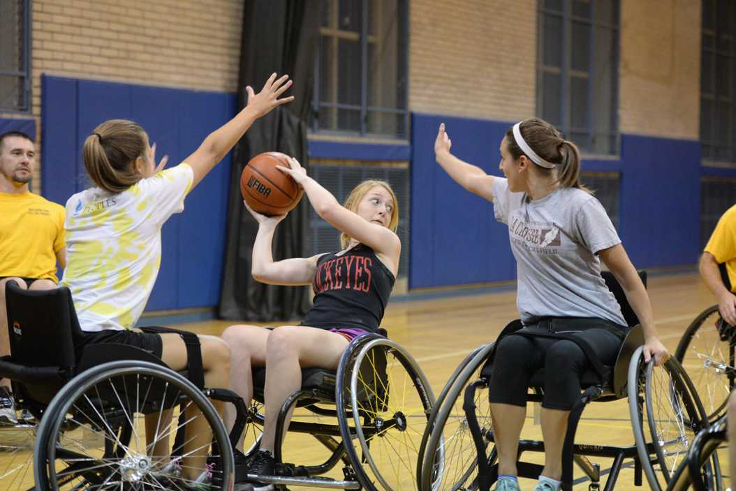 Lainey Elliot, Kelley Schpech, and Jessica Krausenick participate in a five-on-five game of wheelchair basketball in the Bellefield Gym Thursday evening. Theo Schwarz | Senior Staff Photographer