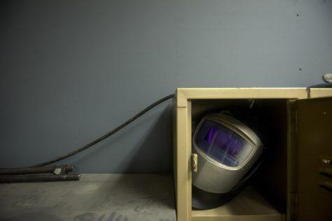 A welding helmet sits in a dusty corner of the shop.