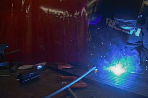 As Miller welds, a red sheet protects the rest of the shop from the extremely bright light of the welding torch.