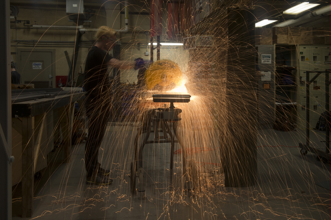 Sparks fly as Sean Gallagher cuts a metal support beam for a set piece. Gallagher and everyone else in the shop wore ear plugs during the cutting.