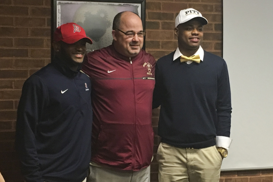 Paris Ford (right) poses Wednesday with his former Steel Valley High School head coach, Rod Steele, and former teammate, Dewayne Murray, after signing his National Letter of Intent. Dominic Campbell | For The Pitt News