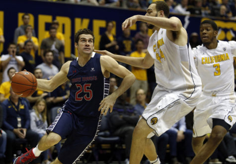 Saint Mary's guard Joe Rahon (25) drives past Cal's Kameron Rooks (44) in the first half at Haas Pavilion in Berkeley, California, on Saturday, Dec. 12, 2015. Cal won, 63-59. (Ray Chavez/Bay Area News Group/TNS)