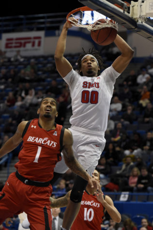 SMU Mustangs forward Ben Moore (0) dunks over Cincinnati Bearcats guard Jacob Evans (1) and guard Troy Caupain (10) during the first half of the 2017 AAC Championship on Sunday, March 12, 2017 at the XL Center in Hartford, Connecticut. (John Woike/Hartford Courant/TNS)