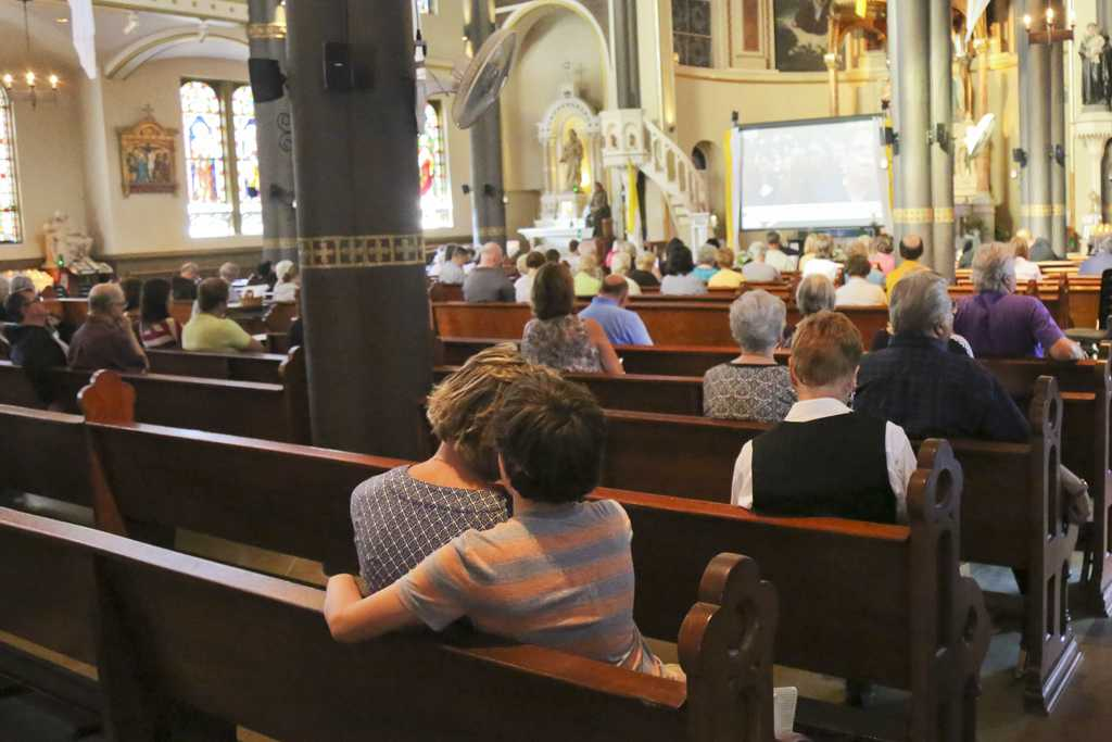 Families at St. Stanislaus Kostka Church listen to a live feed of Pope Francis speak on Sunday.  Theo Schwarz | Senior Staff Photographer