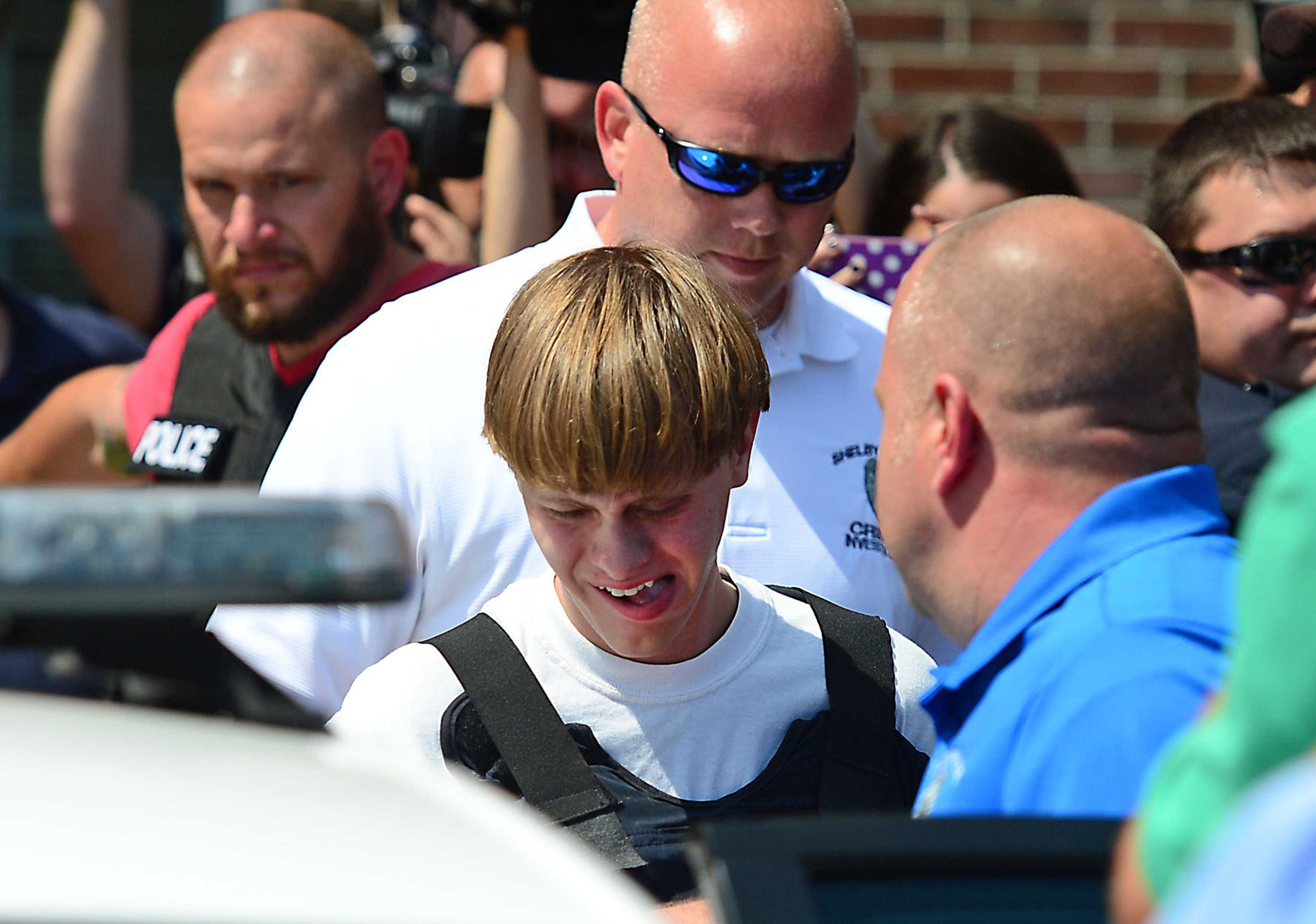Charleston shooting suspect Dylann Roof is escorted from the Shelby Police Dept. Thursday, June 18, 2015 in Shelby, N.C.  (Todd Sumlin/Charlotte Observer/TNS)