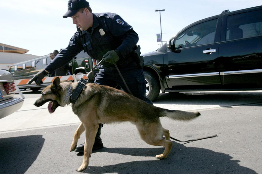 Officer Steven Piel and his bomb sniffing dog, Radar, check cars outside of Fellowship Chapel in Detroit, Michigan, after there were rumors of a bomb threat, Wednesday, April 19, 2006. ( Susan Tusa/Detroit Free Press/KRT)