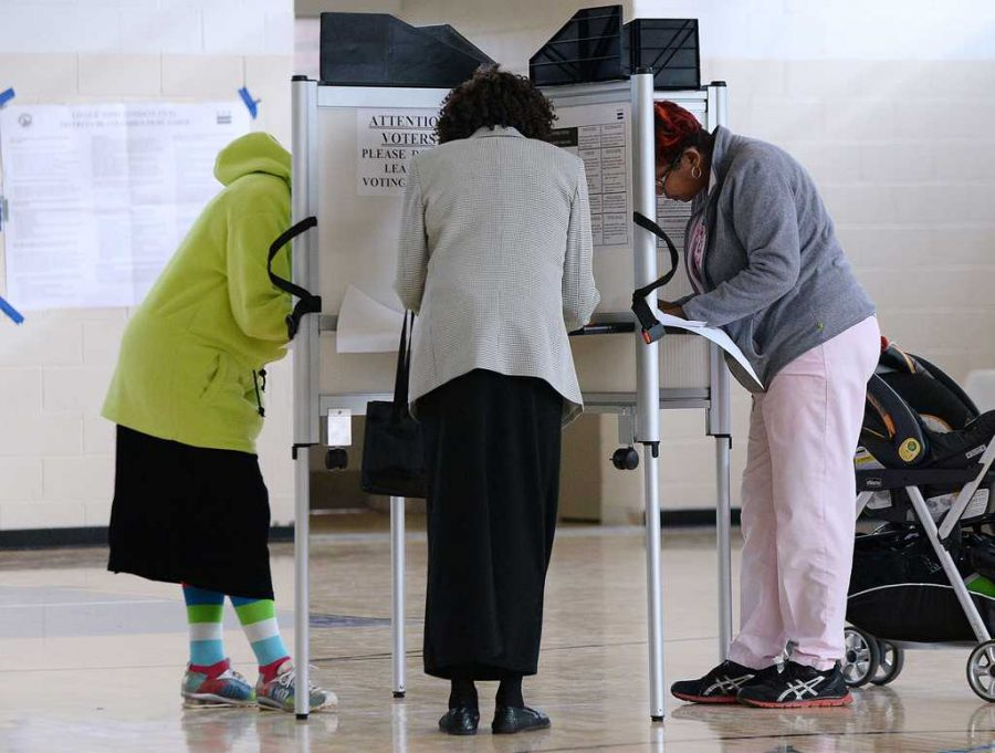 Voters fill out their ballot at a polling station. (Olivier Douliery/Abaca Press/MCT)