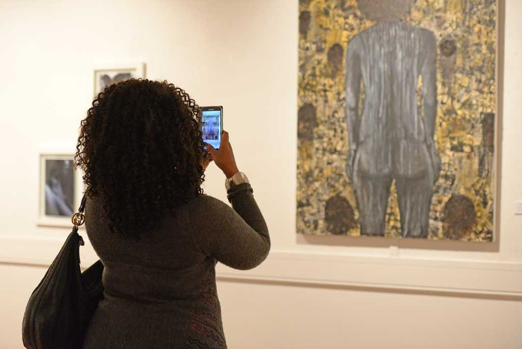 "A reception guest takes a photo of one of the pieces of art in ""Exposure: Black Voices in the Arts."" Meghan Sunners 