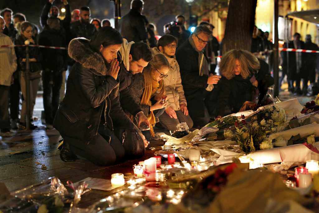 At the Le Bataclan Theater in Paris, people bring flowers to a memorial at a nearby street corner on Saturday, Nov. 14, 2015, as France declares a state of emergency after at least 120 people were killed in gun and bomb attacks. (Carolyn Cole/Los Angeles Times/TNS)