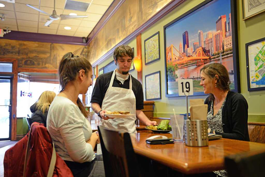 Aaron Kutchner, a server at Red Oak Cafe, serves vegetarian dishes to Kelly Williams (left), a Ph.D student in Public Health, and Adelina Malito (right), a Social Work Master's student.  Nikki Moriello  | Visual Editor