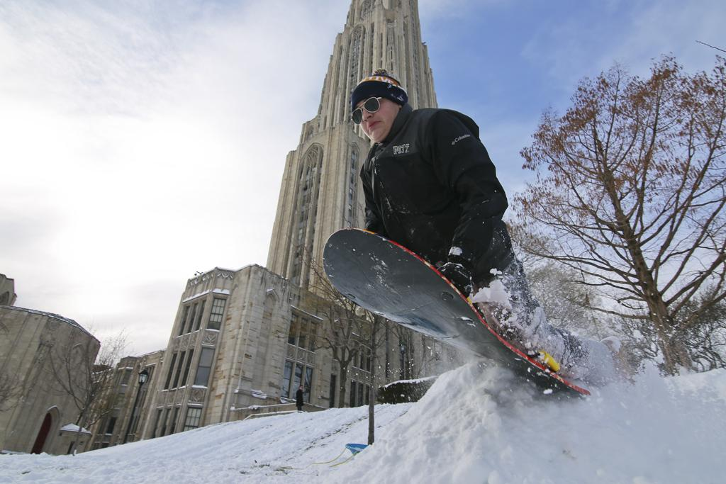 Antonio Narducci launches off a snow bank outside of the Cathedral of Learning Saturday afternoon. Theo Schwarz | Senior Staff Photographer
