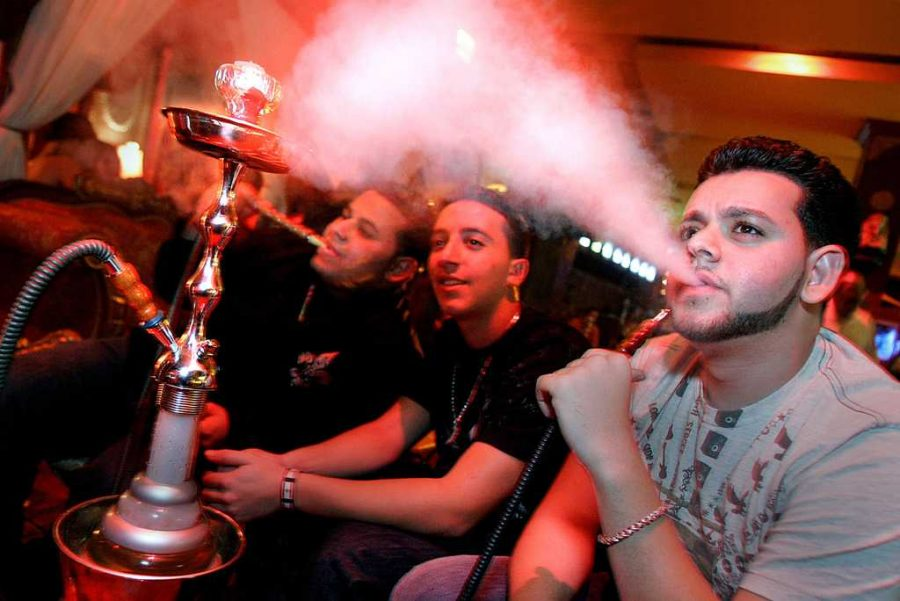 Ammar Zirli, right, puffs on a hookah along with friends Yussef Assaf, center, and Hassan Soueid while sitting at Off The Hookah at Las Olas Riverfront, in Fort Lauderdale, Florida. (J. Albert Diaz/Miami Herald/MCT)