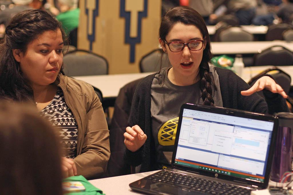 Emilee Betz (right) explaining her team's app to a judge. Emily Brindley for the Pitt News