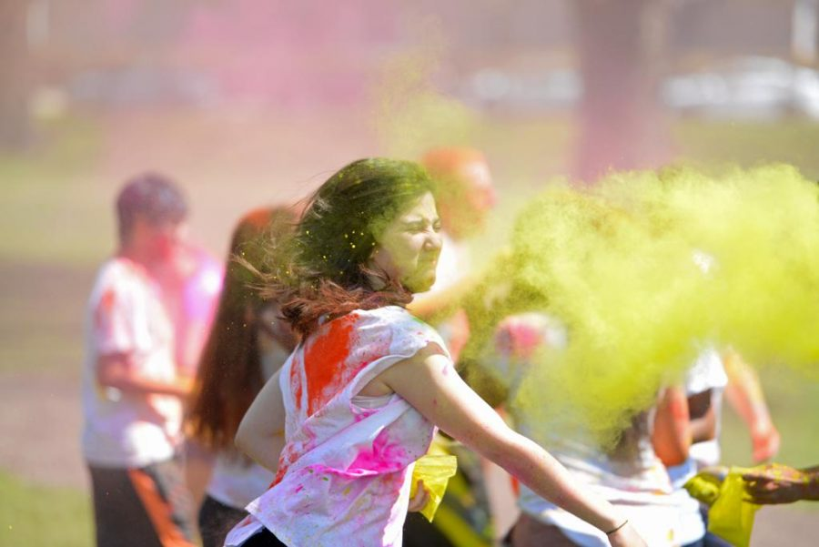 Students throw colored powder in the air at the Holi Festival on Sunday, sponsored by the Hindu Students Council. Kate Koenig | Visual Editor
