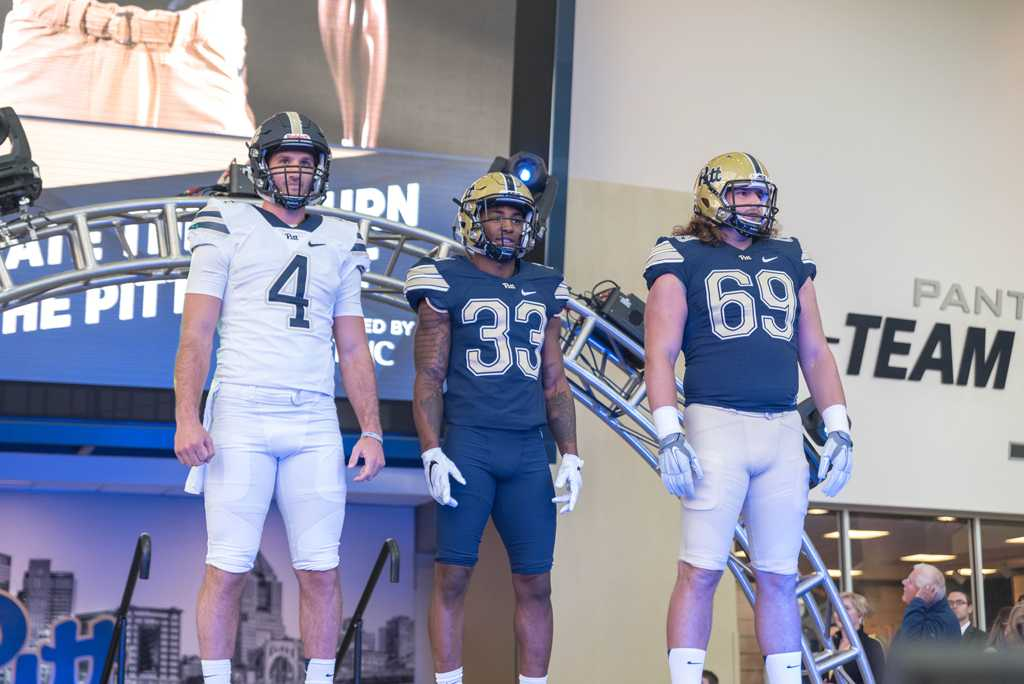 Nathan Peterman (4), Jordan Whitehead (33) and Adam Bisnowaty (69) show off the new Pitt football uniforms. Matt Hawley | Staff Photographer