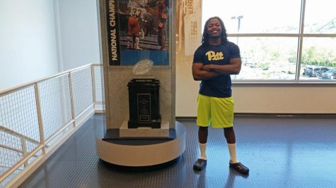 Chawntez Moss poses by the 1976 National Championship trophy at Pitt's football practice facility. Steve Rotstein | Contributing Editor