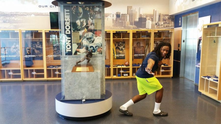 Chawntez Moss poses next to the Heisman Trophy at Pitt's football practice facility. Steve Rotstein | Contributing Editor