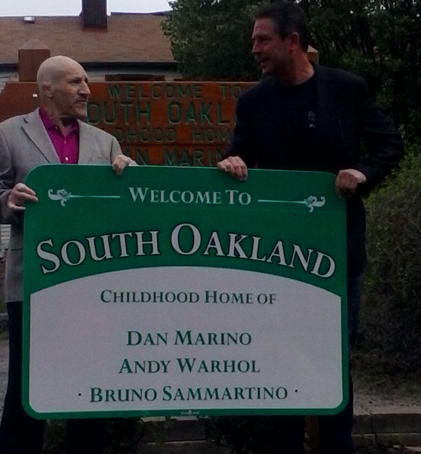 Bruno Sammartino and Dan Marino hold up a sign dedicated to them in 2016. (TPN File Photo)