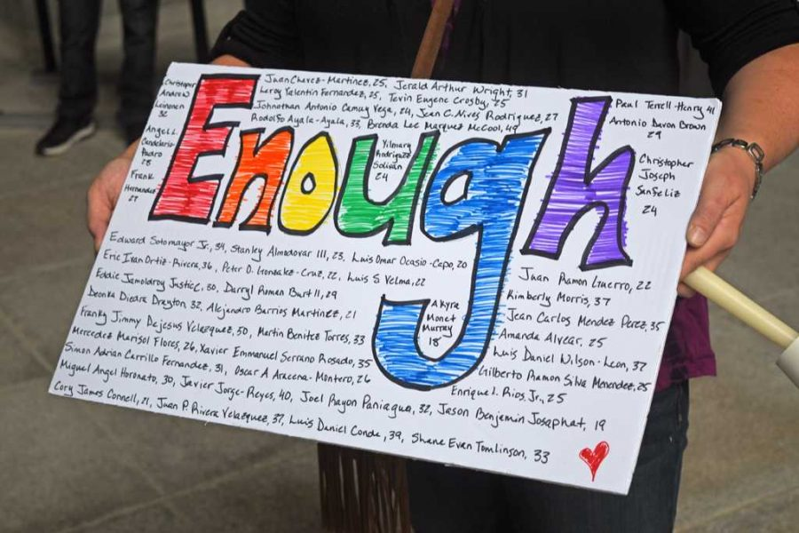 A+person+attending+the+vigil+for+the+victims+of+the+Orlando+mass+shooting+holds+a+sign+that+says+%22enough%22+with+the+49+victims+names+and+ages+written+around+it.+Alex+Nally+%7C+Staff+Photographer