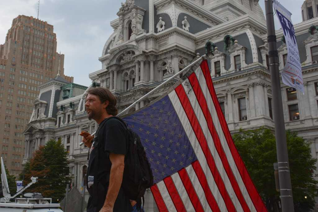 Joel Bradshaw, from Schenectady, New York, carries an upside American flag in Dilworth Plaza. Stephen Caruso | Visual Editor