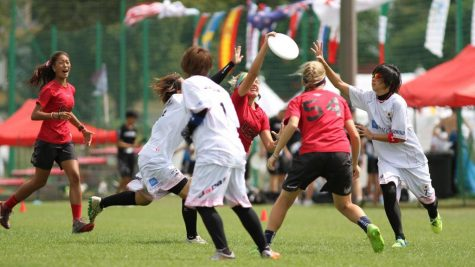 Schreiber, center, with disc, lays out for a disc during the USA U-20 team's game against Japan in Wroclaw, Poland this August. Courtesy of Katie Schreiber
