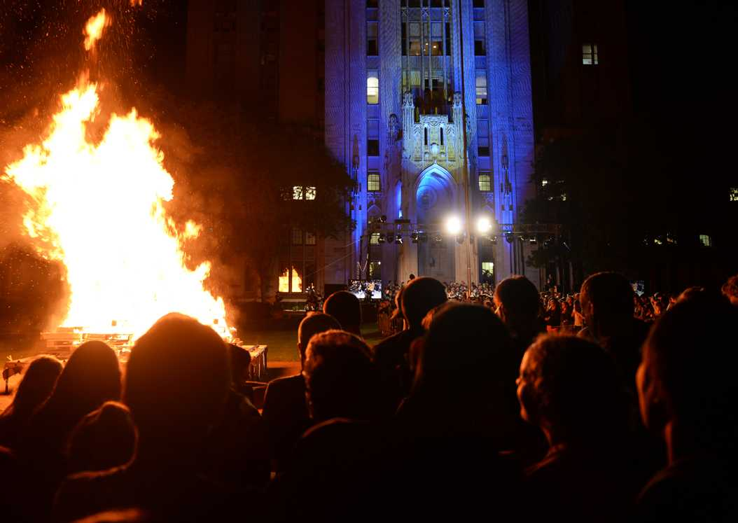 Thursday night's bonfire glowed in front of the blue and gold lights on the Cathedral of Learning. | Meghan Sunners / Senior Staff Photographer