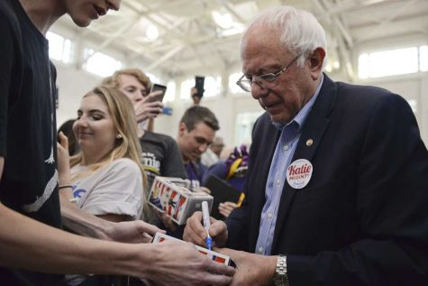 Bernie Sanders signs Bernie Sanders action figures at a visit earlier this year.   John Hamilton | Staff Photographer