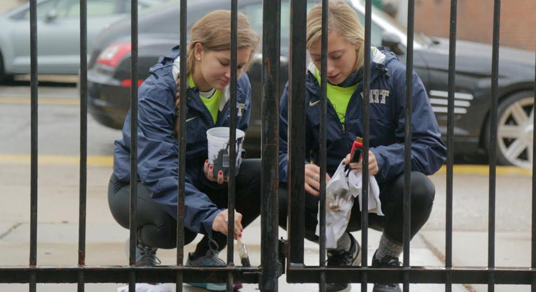 Two Pitt students paint a fence outside Phillips Elementary School in the South Side on Pitt Make a Difference Day, Oct 22, 2016. Theo Schwarz | Senior Staff Photographer
