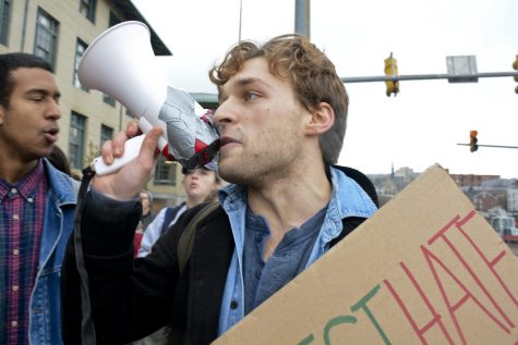 William Brosnahan, a junior at Carnegie Mellon, leads a chant as the march against hate heads up Forbes Avenue towards CMU. Stephen Caruso | Online Visual Editor