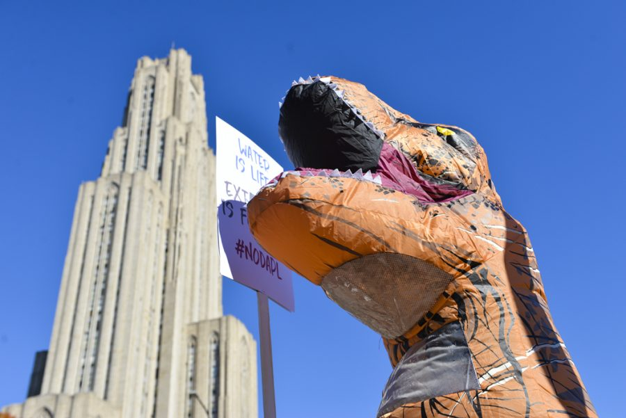 One+protester%2C+dressed+as+a+dinosaur%2C+held+a+sign+proclaiming%2C+%22Water+is+life%2C+extinction+is+forever.%22+Stephen+Caruso+%7C+Senior+Staff+Photographer