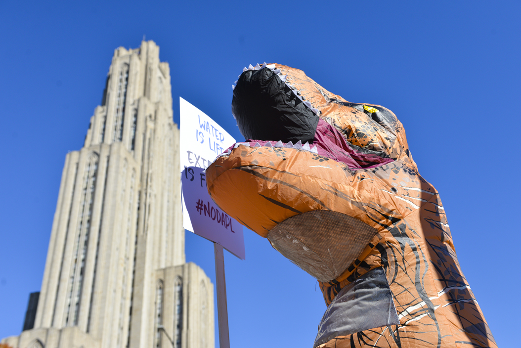"""One protester, dressed as a dinosaur, held a sign proclaiming, """"Water is life, extinction is forever."""" Stephen Caruso 