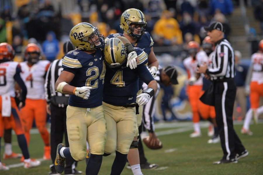Pitt RB James Conner (24) hugs QB Nathan Peterman (4) after Peterman's 13-yard touchdown run late in the first half. Steve Rotstein | Contributing Editor