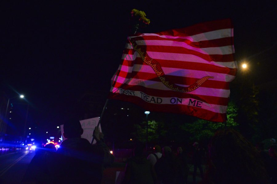 "With cop cars leading the way to create a moving blockade, the protesters fiollowed. Rob Helwis, a part time student at Pitt, waved a ""don't tread on me"" flag as he marched. ""This flag has been around a lot longer than the Tea Party,"" Helwis said. Stephen Caruso 