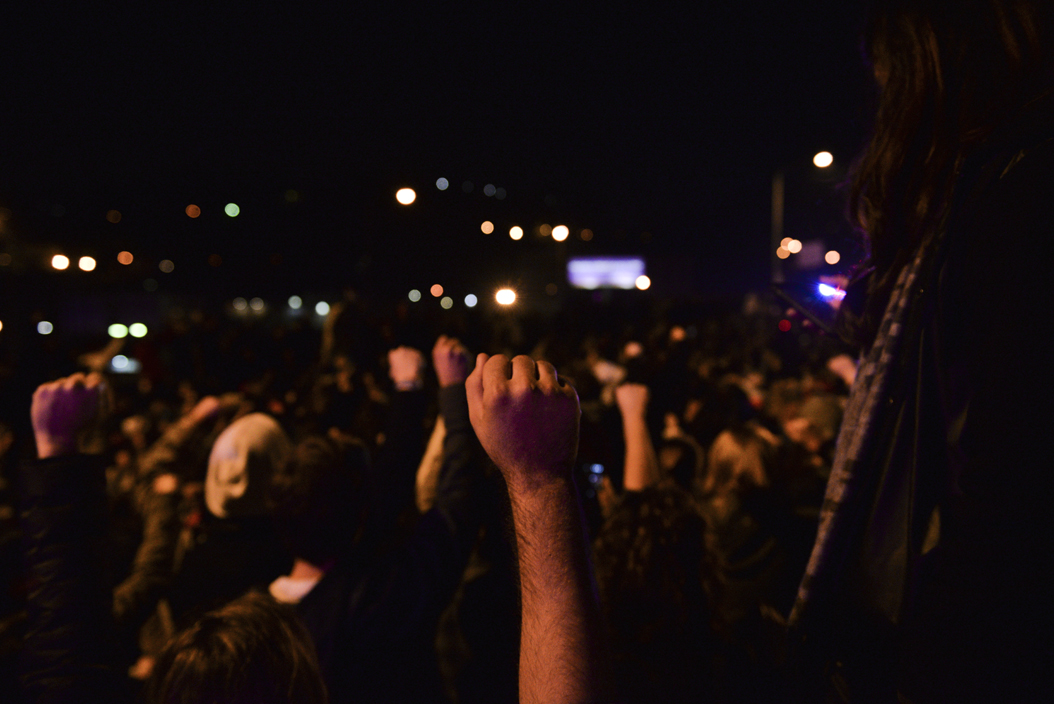 A protester raises a fist in solidarity during a moment of silence on the Birmingham Bridge for victims of hate crimes following the election of Donald Trump. Stephen Caruso | Online Visual Editor