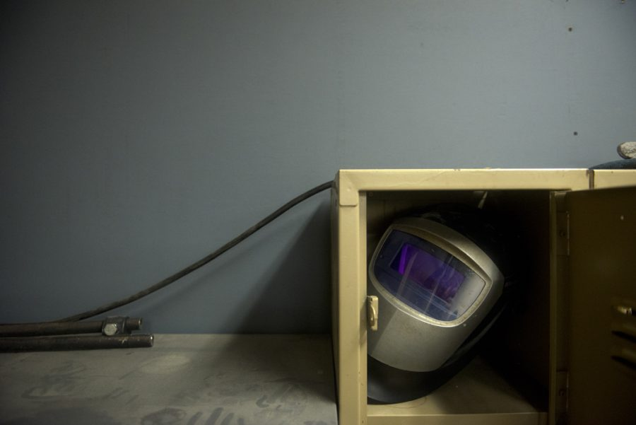 A welding helmet sits in a dusty corner of the shop.