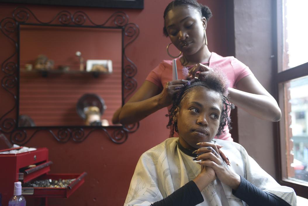 Kamaria Mitchell braids Shaiquia Covington's hair. Covington, of McKeesport, Pa., heard about The Natural Choice through social media. Katie Krater | Staff Photographer