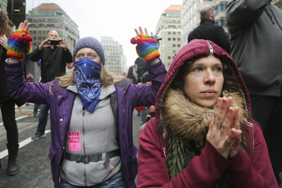 Protesters look towards a line of police in riot gear. Theo Schwartz | Senior Staff Photographer