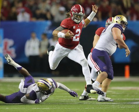 Alabama quarterback Jalen Hurts (2) hurdles a defender in the Crimson Tide's 24-7 national semifinal victory against Washington. Curtis Compton/Atlanta Journal-Constitution/TNS