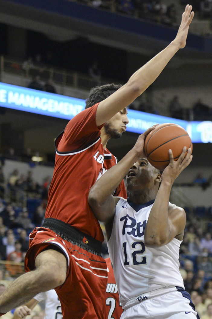 Pitt senior Chris Jones is tightly defended as he attempts to make a rare basket for the Panthers en route to a 106-51 loss to Louisville. Evan Meng   Staff Photographer