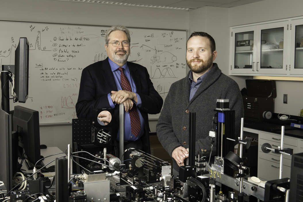 David R. Williams, Director, Center for Visual Science and Professor, Optics, Ophthalmology, Biomedical Engineering, Brain & Cognitive Sciences at the University of Rochester, left, and his former student Ethan A. Rossi, assistant professor of Ophthalmology at the University of Pittsburgh School of Medicine photographed in Williams' lab at the University of Rochester Medical Center January 9, 2017. Courtesy of J. Adam Fenster/University of Rochester