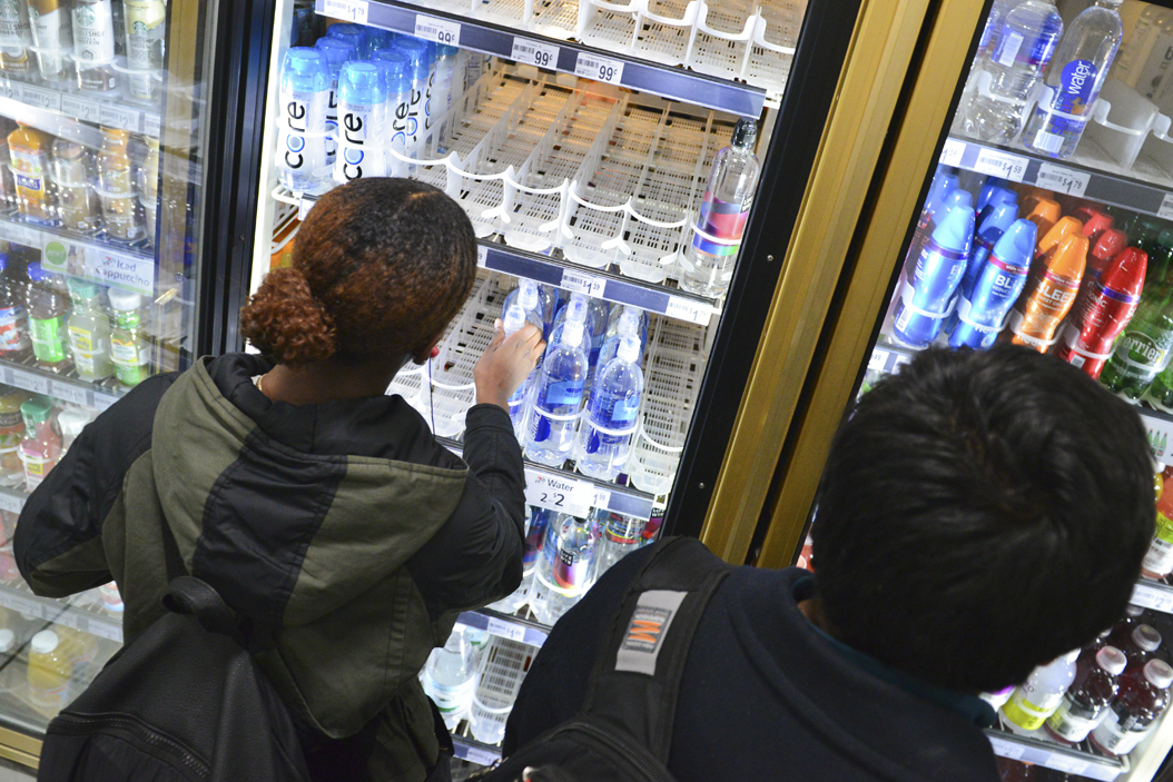 Ashley Brown, a junior neuroscience major, reaches into a cooler to buy water for her and her sorority sisters after a water alert was issued by the city of Pittsburgh on Tuesday evening. Stephen Caruso | Online Visual Editor