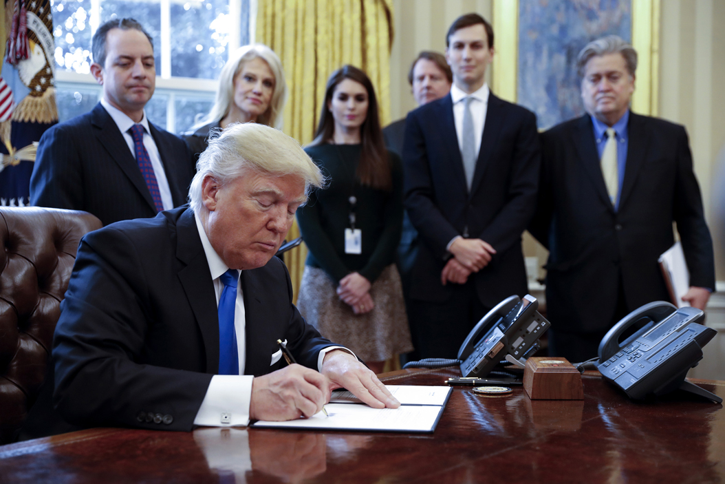 US President Donald Trump, with White House chief of staff Reince Pribus, from left, counselor to the President Kellyanne Conway, White House Communications Director Hope Hicks, Senior Advisor Jared Kushner and Senior Counselor Stephen Bannon, signs one of five executive orders related to the oil pipeline industry in the oval office of the White House Tuesday, Jan. 24, 2017 in Washington, D.C. President Trump has a full day of meetings including one with Senate Majority Leader Mitch McConnell and another with the full Senate leadership. (Pool/Abaca Press/TNS)