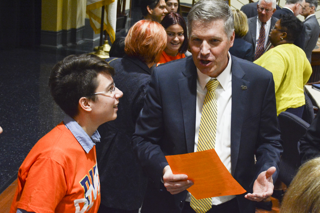 Chancellor Patrick Gallagher talks to members of the Fossil Free Pitt Coalition, wearing orange t-shirts over formal dress, at Pitt's winter Board of Trustees Meeting at the William Pitt Union on Friday. Stephen Caruso | Staff Photographer
