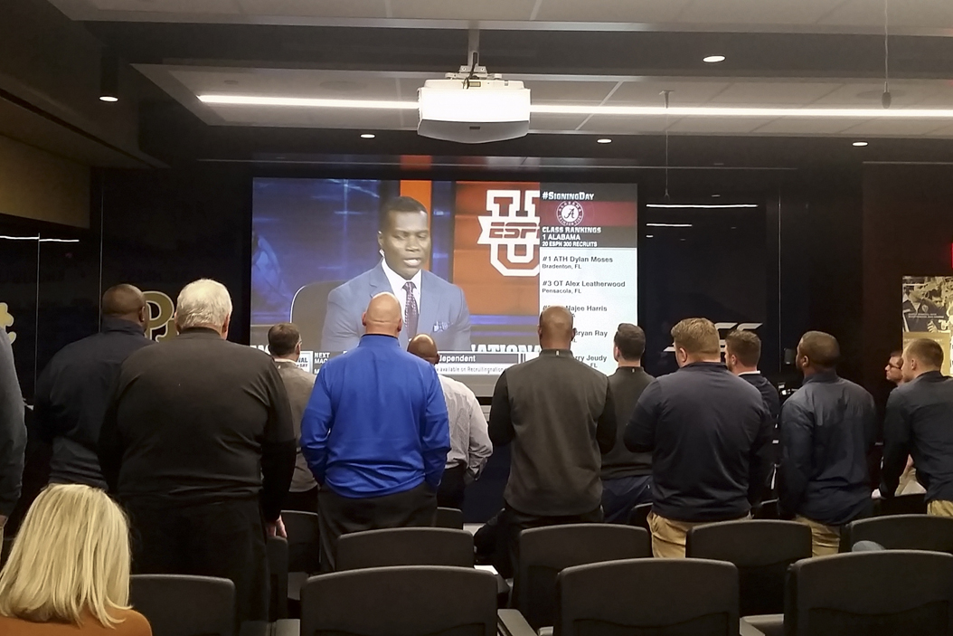 Pitt's football coaching staff gathers in the team room to watch running back A.J. Davis announce his college decision live on ESPN2 Wednesday afternoon. Steve Rotstein | Contributing Editor