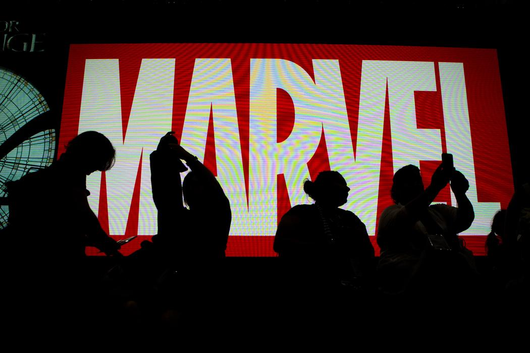 Attendees sit in front of an illuminated Marvel sign during the second day of Comic-Con 2016. (Harrison Hill/Los Angeles Times/TNS)