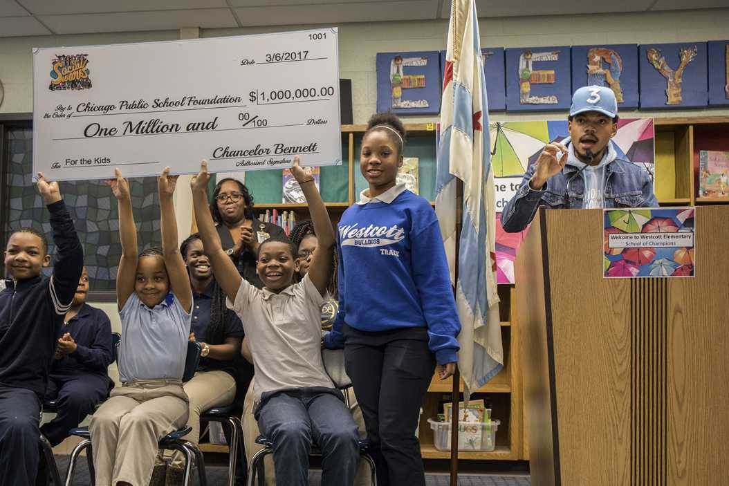 Students hold up a check for $1 million dollars from Chance the Rapper, right, who holds a press conference at Westcott Elementary School in Chicago's Chatham neighborhood on March 6, 2017. (Zbigniew Bzdak/Chicago Tribune/TNS)