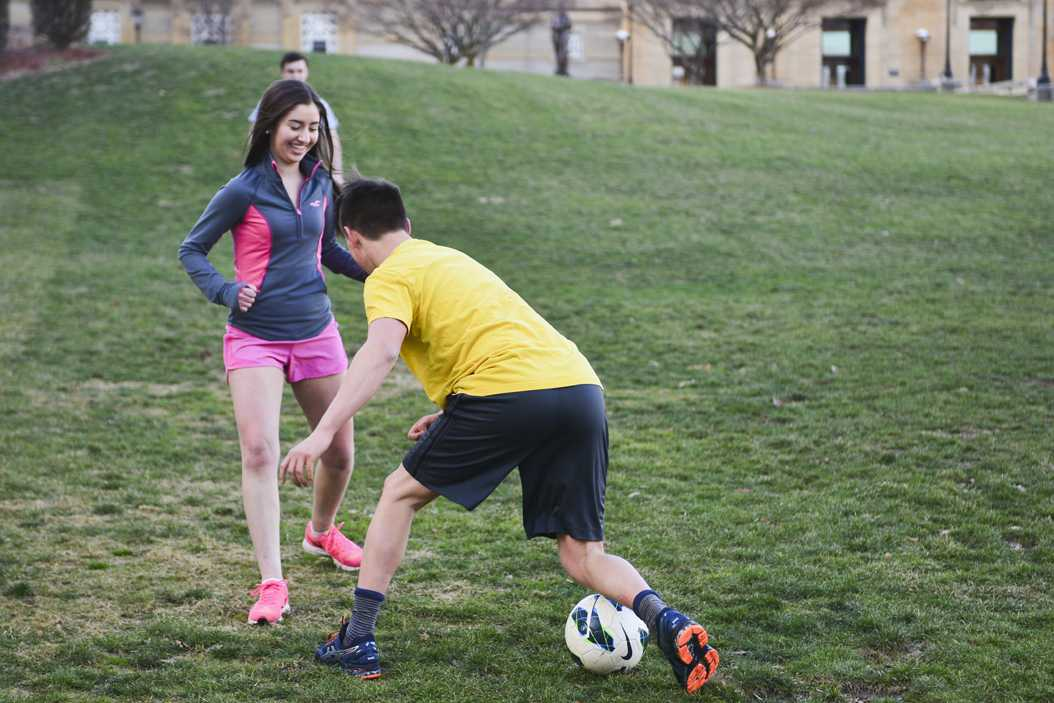 Taking advantage of the warm weather, first-years Sheridan Feck and Kiel Hillock play soccer on the Soldiers and Sailors Memorial lawn on Feb. 6. Anna Bongardino | Staff Photographer